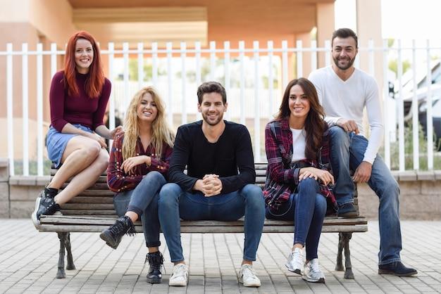 Amis assis sur un banc en bois dans la rue Photo gratuit