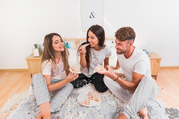 Amis, assis sur un lit avec des plumes à tartiner mangeant des pizzas Photo gratuit