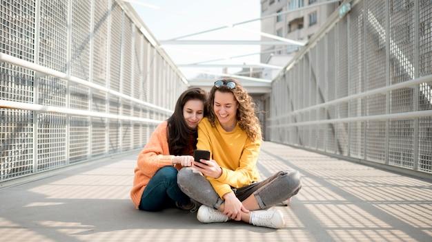 Amis Assis Sur Un Pont Et Regardant Leur Téléphone Photo gratuit