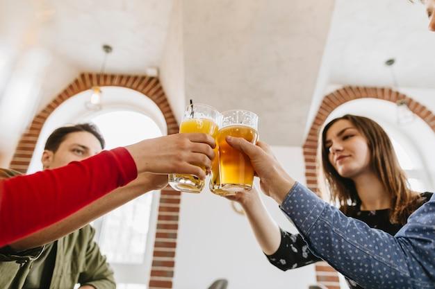 Amis ayant de la bière au restaurant Photo gratuit