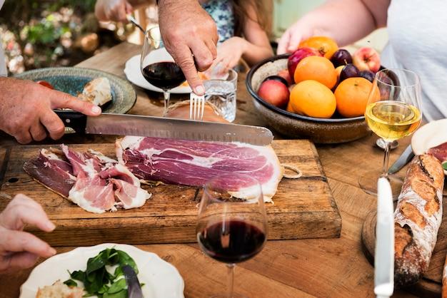 Amis ayant de la charcuterie et du vin pour le dîner Photo Premium