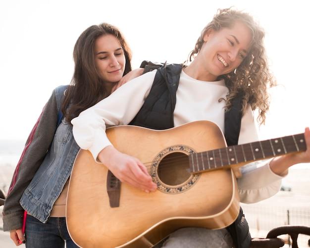 Amis De Basse Vue Jouant De La Guitare Photo gratuit