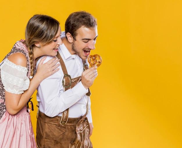Amis bavarois essayant un bretzel Photo gratuit