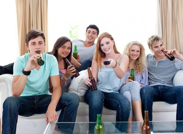 Amis, boire de la bière à la maison et regarder la télévision Photo Premium