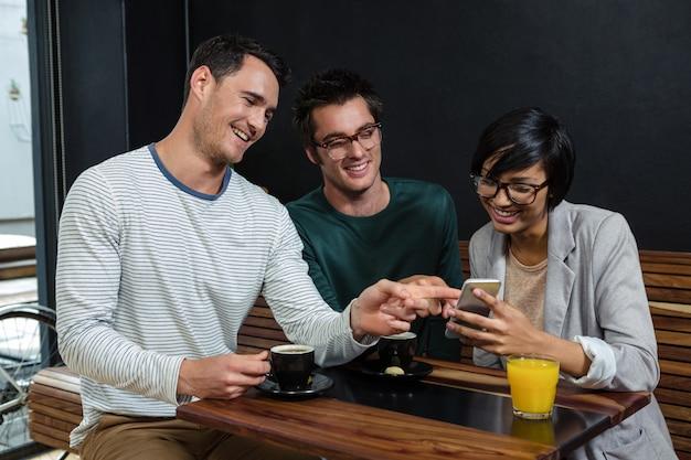 Amis, Boire Du Café Et Du Jus D'orange Tout En Regardant Le Smartphone Photo Premium