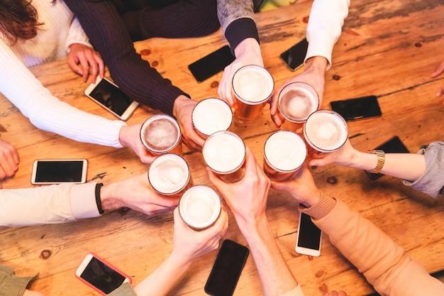 Amis buvant et en grillant de la bière au pub Photo Premium