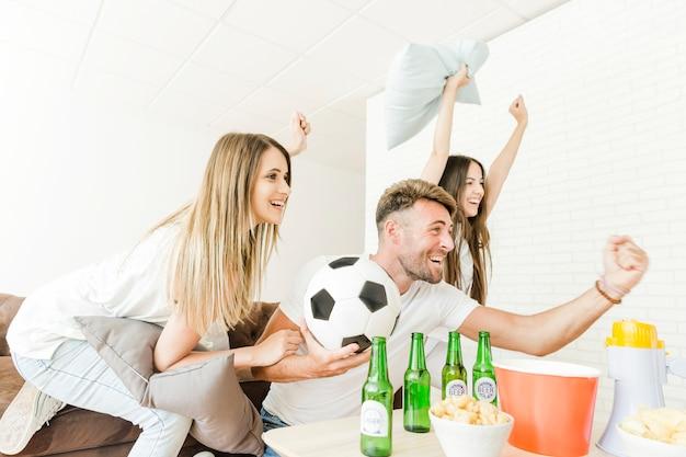 Amis célébrant en regardant le football à la maison Photo gratuit