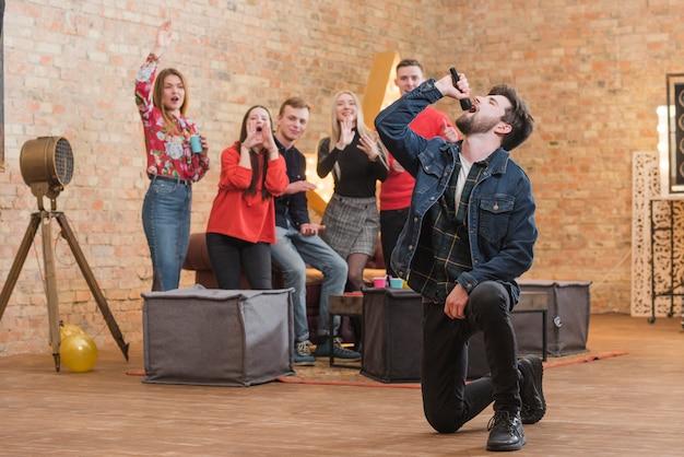 Amis chantant au karaoké lors d'une fête Photo gratuit