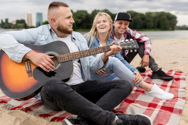 Amis Chantant Et Jouant De La Guitare à L'extérieur Photo gratuit
