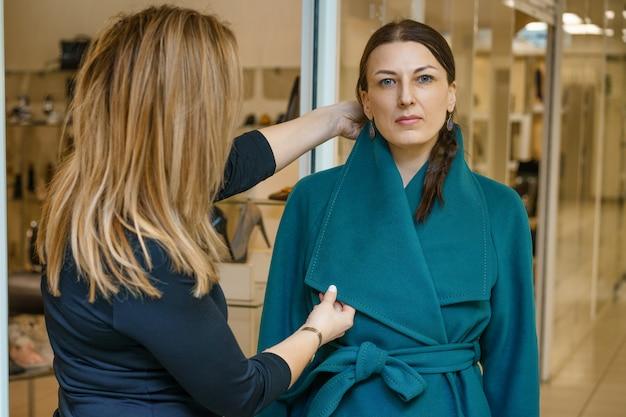 Amis choisissent un manteau dans le magasin Photo Premium