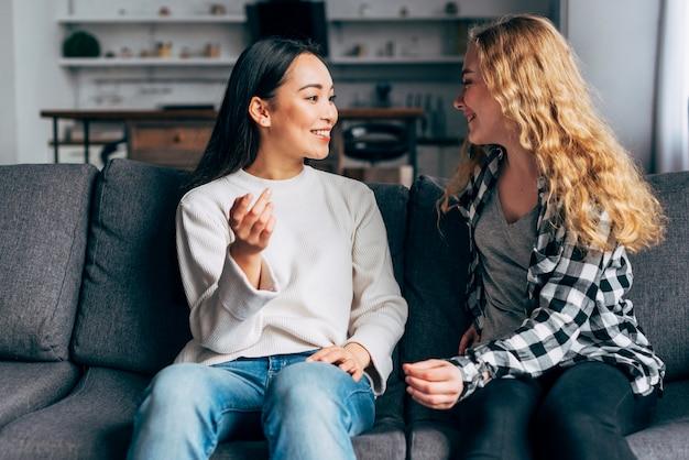 Amis communiquent assis sur un canapé Photo gratuit