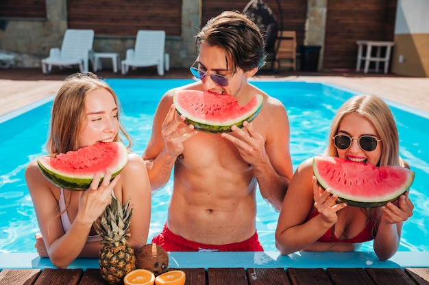 Amis à coup moyen manger de la pastèque dans la piscine Photo gratuit