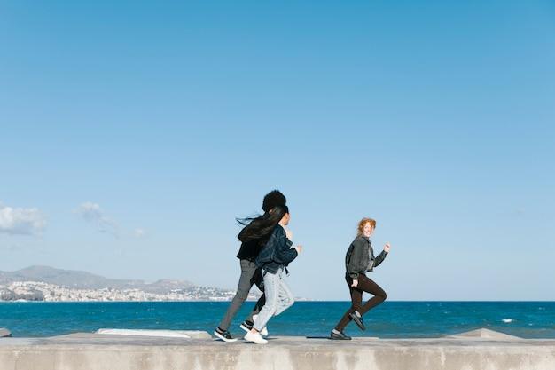 Amis courir devant la mer Photo gratuit