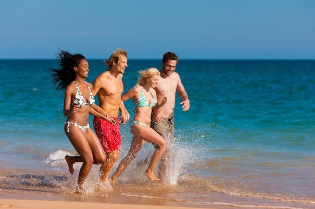 Amis en cours d'exécution sur la plage Photo Premium