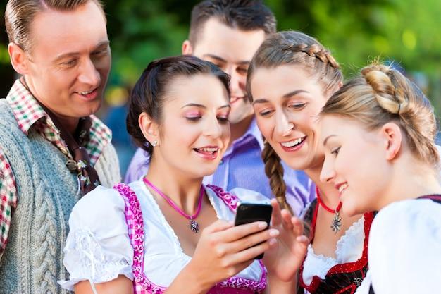 Amis dans le jardin de bière avec smartphone Photo Premium