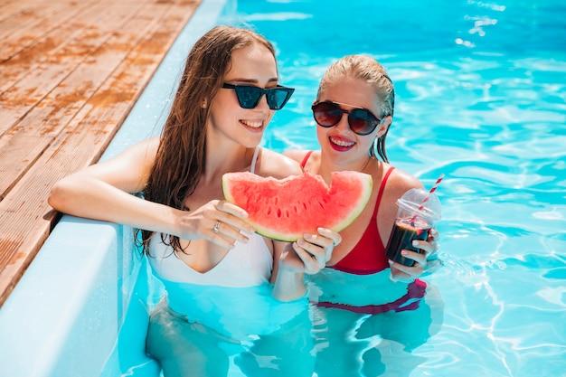 Amis dans la piscine tenant une pastèque Photo gratuit