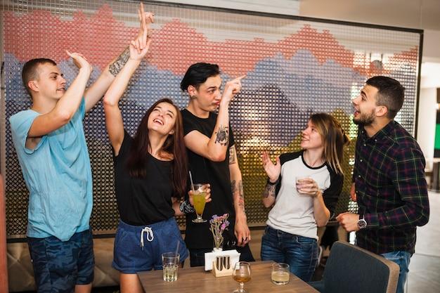 Amis dansant et appréciant des boissons au restaurant Photo gratuit
