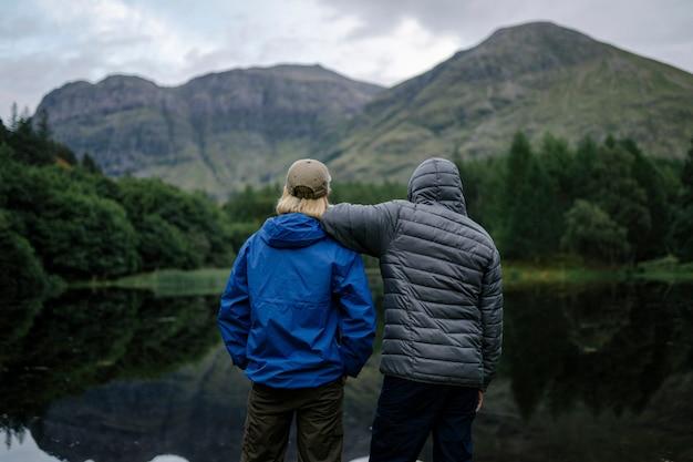 Amis debout au bord de la rivière dans les highlands Photo Premium