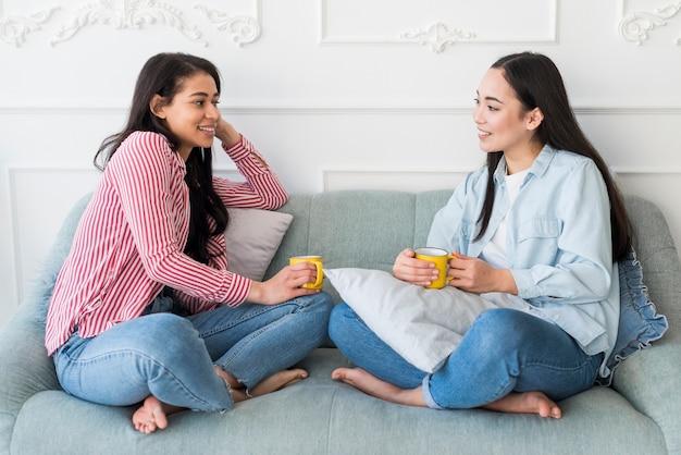 Amis Discutant Assis Sur Un Canapé Photo gratuit