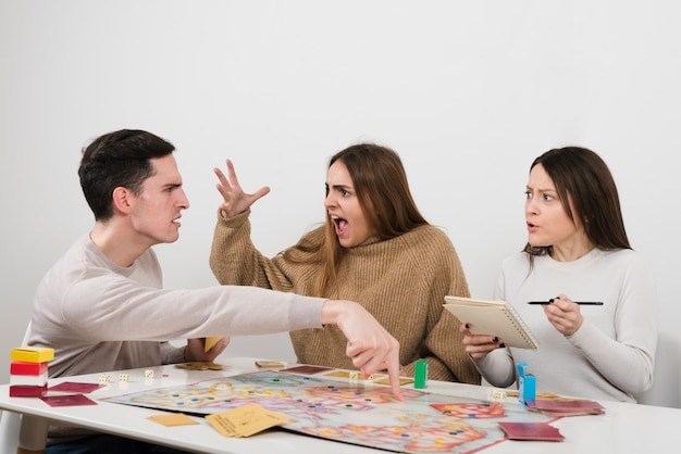 Amis discutant sur un jeu de société Photo gratuit