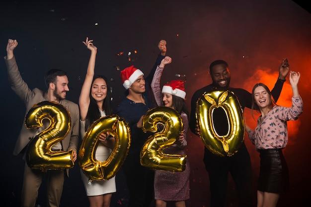 Amis excités posant avec des ballons à la fête du nouvel an Photo gratuit