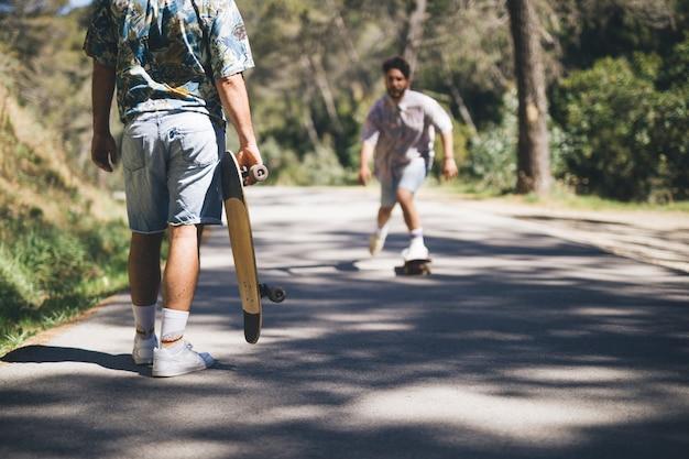 Amis, faire de la planche à roulettes sur la route forestière Photo gratuit