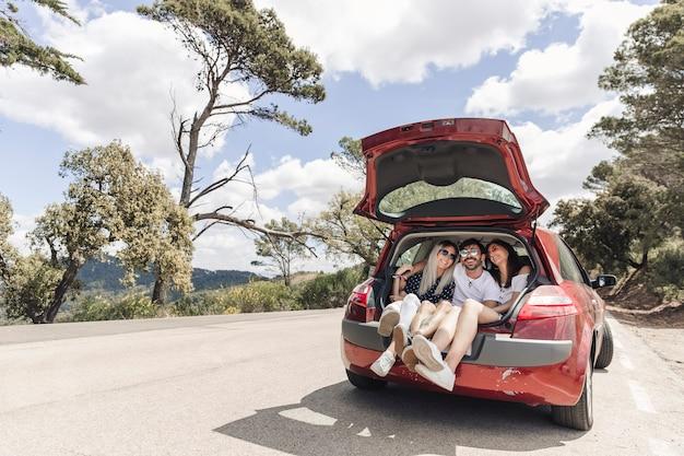 Amis faisant plaisir dans le coffre de la voiture sur la route Photo gratuit