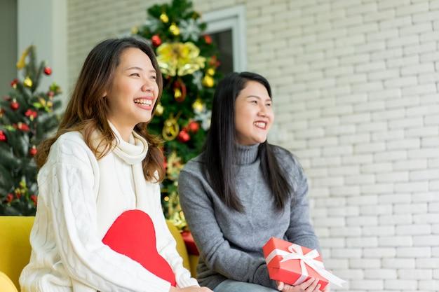 Amis de femmes asiatiques assis sur un canapé et rire ensemble dans le salon pour la célébration de noël Photo Premium