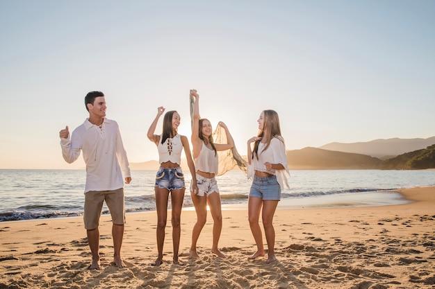 Amis fêtant sur la plage Photo gratuit