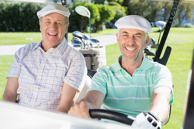 Amis de golf conduisant dans leur voiturette de golf souriant à la caméra Photo Premium