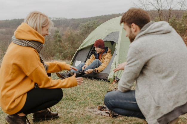 Amis de grand angle en voyage avec feu de camp Photo gratuit