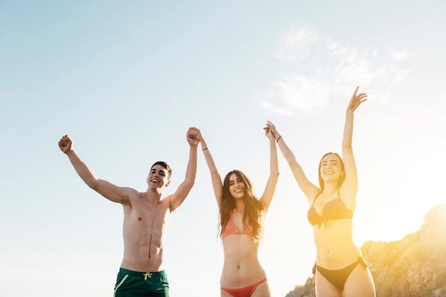 Amis, levant les bras à la plage Photo gratuit