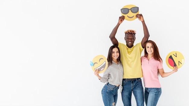 Amis ludiques tenant un espace de copie emoji Photo gratuit