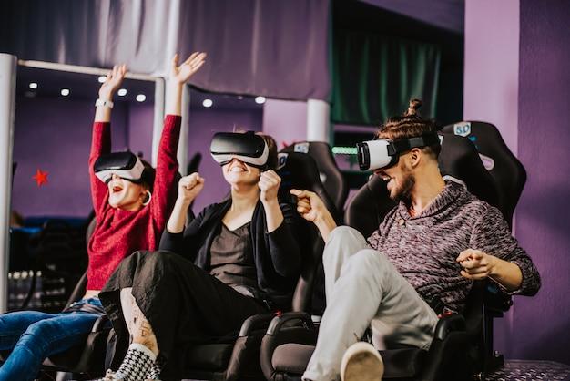 Amis à lunettes virtuelles regardant des films au cinéma avec effets spéciaux en 5d Photo Premium