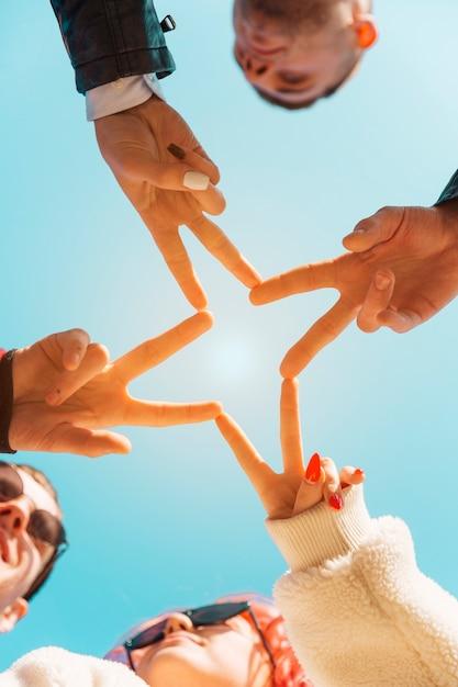 Amis mains mettant ensemble avec le geste de la paix Photo gratuit