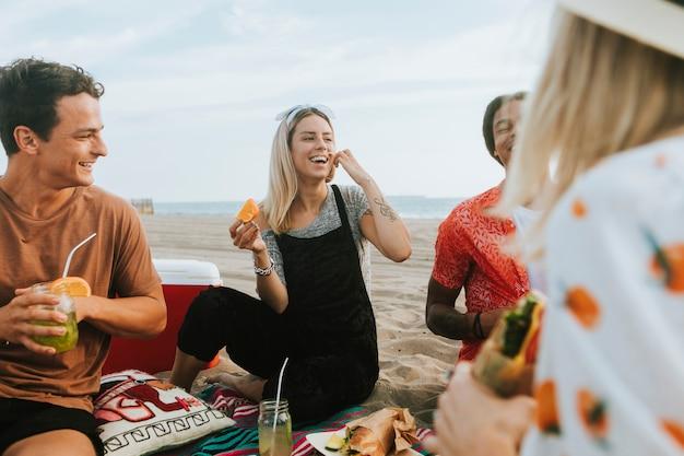 Amis, Manger De La Nourriture Lors D'un Pique-nique à La Plage Photo Premium