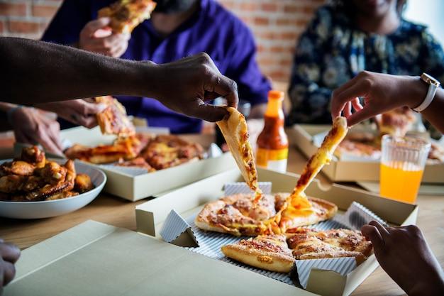 Amis, manger de la pizza ensemble à la maison Photo Premium