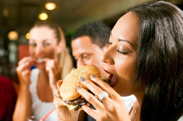 Amis, Manger De La Restauration Rapide Dans Un Restaurant Photo Premium