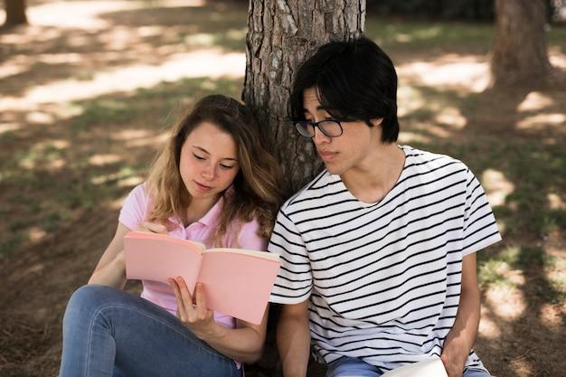 Amis multiethniques lisant un cahier et s'appuyant sur un arbre Photo gratuit