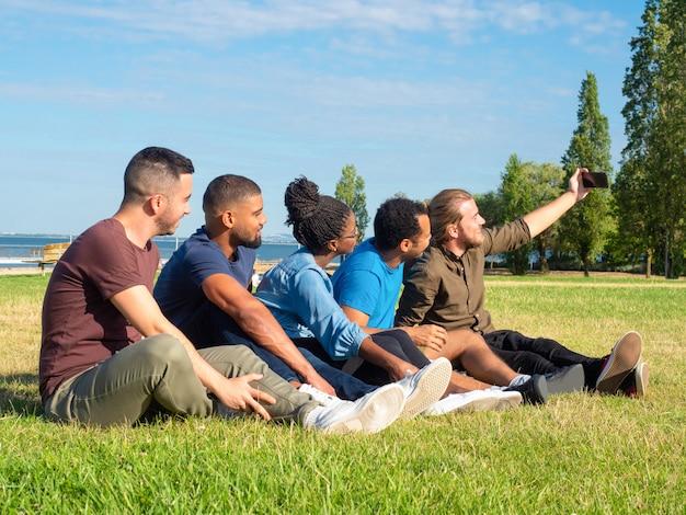 Amis multiethniques prenant selfie dans le parc Photo gratuit
