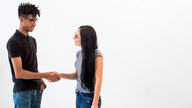 Amis multiethniques se serrant la main sur une surface blanche Photo gratuit