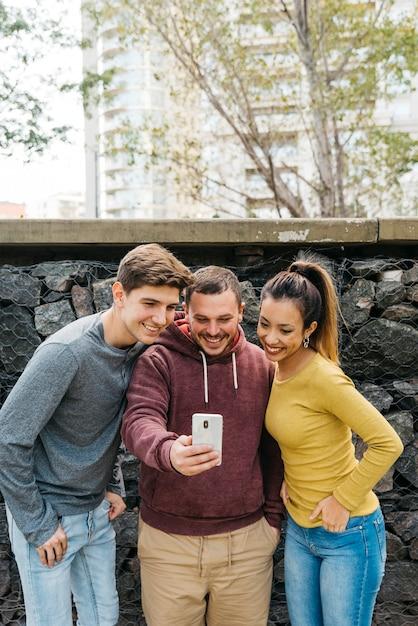 Amis multiraciales prenant selfie près d'une clôture de pierre Photo gratuit
