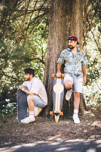 Amis avec des planches à roulettes en forêt Photo gratuit