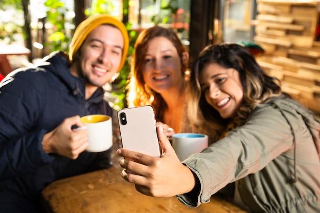 Amis prenant un selfie au café Photo gratuit