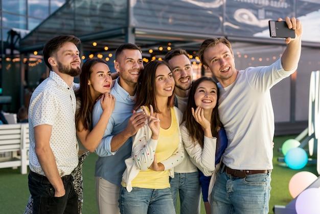 Amis prenant un selfie lors d'une fête Photo gratuit