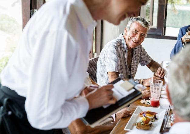 Amis prenant son petit déjeuner dans un hôtel Photo Premium