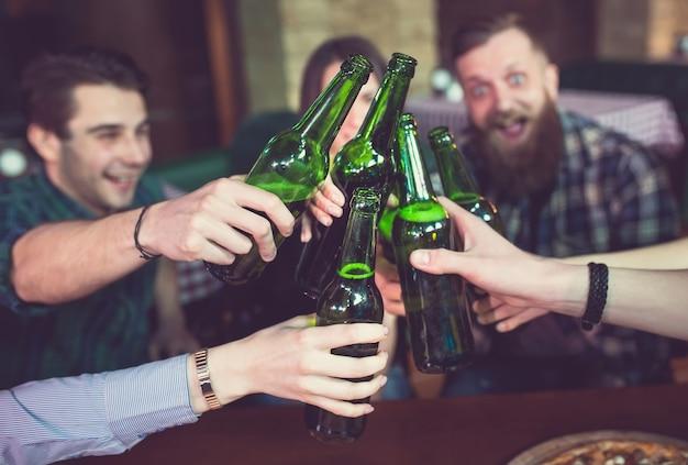 Amis prenant un verre dans un bar, ils sont assis à une table en bois avec des bières et des pizzas. Photo Premium