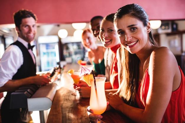 Amis profitant de boissons sur le comptoir de bar dans une discothèque Photo Premium