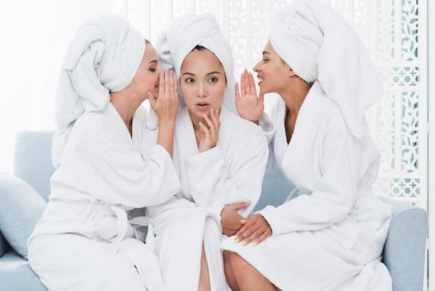 Amis racontant des secrets dans un spa Photo gratuit