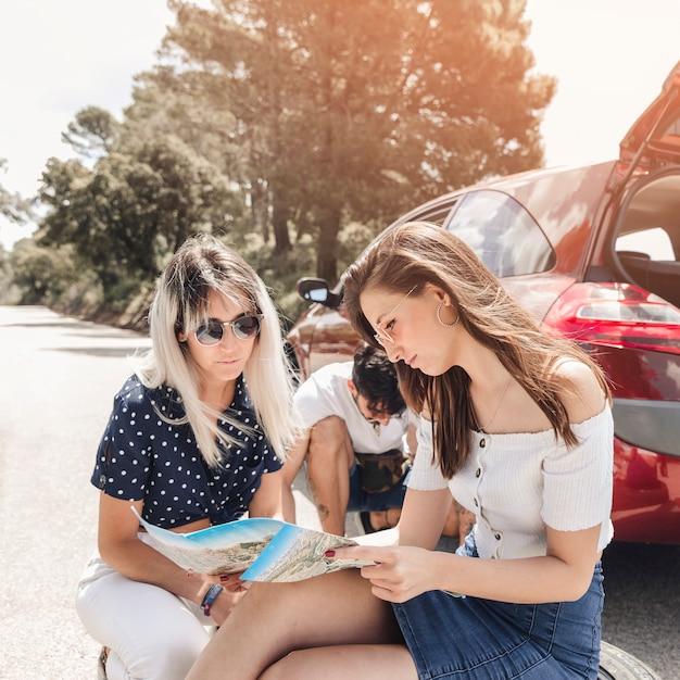 Amis en regardant la carte près de la voiture en panne Photo gratuit